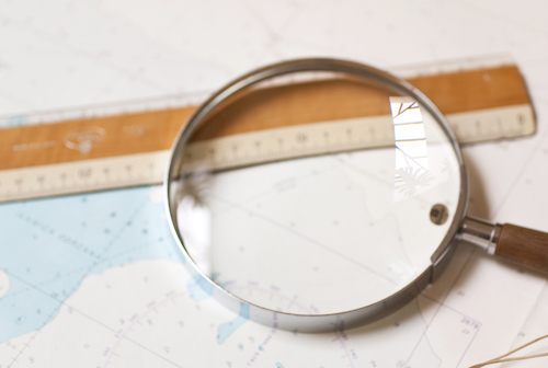 Ruler, magnifying glass, on top of map