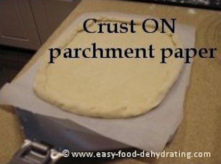 Pizza crust on parchment paper, atop a huge spatula
